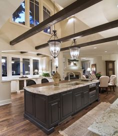 love this open kitchen  exposed beams & wood floors
