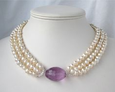 Freshwater Pearl Necklace,   A faceted egg-shaped lavender crystal sits in three strands of ivory freshwater pearls. 17.75 inches
