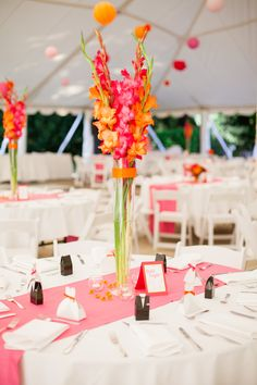 Tall centerpieces add drama without blocking conversation.  Use orange and hot pick Gladioli in skinny crystal vases. Flowers by A Floral Affair www.afloralaffair.... Photography by Gabriela Ines www.gabriela-ines.com.