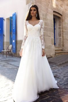 Stunning floral applique sheer long sleeve wedding dress with tulle skirt; Featured Dress: TM Crystal Design