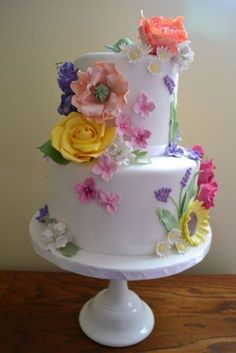 I like how the flowers on this cake are all different types, colors and sizes... very whimsical.
