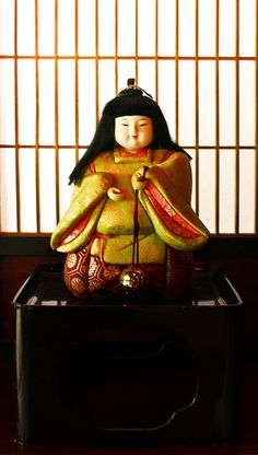 Japanese Kimekomi doll - Kimekomi refers to a method of making dolls. They start with a carved and/or molded base of wood or wood compo. A design of different patterned cloth scraps is planned out, and the base is grooved so that the edges of the cloth can be hidden in the grooves. The cloth is glued on and the edges tucked in. The head and hands (if any) of the doll are usually finished with gofun; the hair may be part of the molded head or be a separate wig.