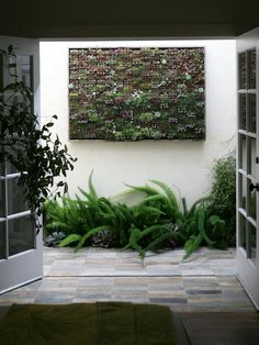 This+tiny+alleyway+didn't+have+much+room+for+a+garden.+Designer+Seth+Boor+made+use+of+the+space+off+of+the+bedroom+by+designing+a+custom+succulent+garden+wall+hanging.+The+garden+wall+adds+an+unexpected+touch+over+a+bed+of+asparagus+fern.+