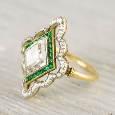 This truly remarkable vintage engagement ring is made in PLATINUM on gold and centered with an approximate 2.80 CARAT EGL certified old european cut diamond with I-J color and SI1 clarity. Center diamond is set in an EDWARDIAN setting accented by calibre cut emeralds and single cut diamonds