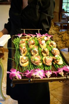 tray lined with chinese scallions (?) and orchids.
