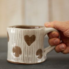 This robust mug is decorated with polka dots and a heart on one side. It is 3 1/4 inches tall, 3 3/4 inches wide at the top, and holds about 12 liquid ounces. Wheel-thrown in our Vermont studio from brown stoneware clay, dipped in white slip (liquid clay), and glazed a glossy clear. The inside of the piece is a smooth chocolate brown color.  This is a representative photo; you will receive either this exact piece or one VERY similar to the piece in the listing photo.  Your purchase...