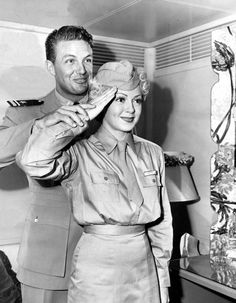 Navy Lieutenant Robert Stack teaches Lana Turner how to salute. October, 1944