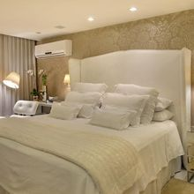 Quarto de casal com cabeceira da cama estofada e papel de parede
