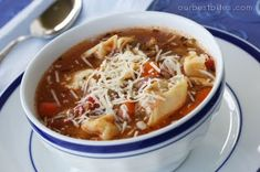 Tortellini Sausage Soup 3 links Italian sausage 4 cloves pressed garlic 1 onion, diced ½ c. water 2 15-oz. cans chicken broth ½ c. apple cider 1 16-oz. can diced tomatoes 1 8 oz. can tomato sauce 1 c. sliced carrots 1 tsp. dried basil 1 tsp. dried oregano 2 medium zucchini, grated  2 tablespoons dried parsley 8-10 oz. package cheese tortellini  2 Tbsp. dried parsley