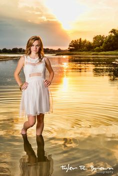 Hadlie stands in shallow water as the sun sets behind her for this stunning senior portrait.