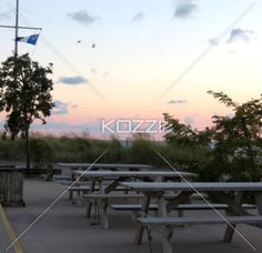 A row of picnic tables on a patio beside the beach at sunset.