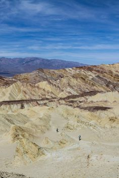 A couple of hikers explore the badlands below Zabriskie Point in Death Valley National Park, California.