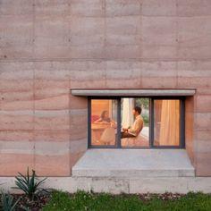 Rammed earth walls with striated patterns  frame Tatiana Bilbao's Ajijic House