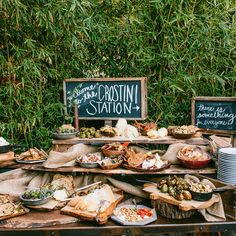 A build-your-own crostini station with breads, toppings, and sides served on wooden platters and earthy tableware.