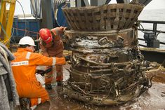 Bezos Expeditions crew members work with the thrust chamber of a recovered F-1 rocket engine from the Saturn V rocket that launched one of NASA's historic Apollo moon missions in this photo. Billionaire Jeff Bezos financed the recovery effort in the Atlantic Ocean and announced its success on March 20, 2013.