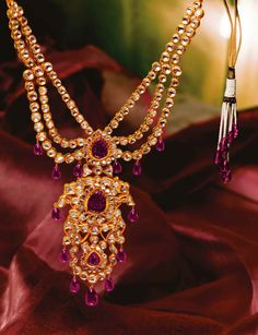An extravagant ensemble of polki in kundan setting and rich ruby drops forming a splendid necklace.