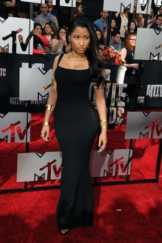 Nicki Minaj at the 2014 MTV Movie Awards in a skintight black dress with sheer paneling along the sides and a serious set of gold accessories.
