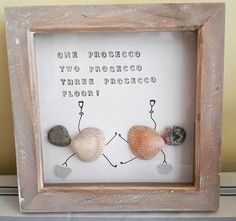 This is a fun pebble art picture 2 drunk women lying on the floor, made from sea shells & pebbles found on an Anglesey beach Using the funny saying: One prosecco, two prosecco, three prosecco, floor! The saying is stamped on with hand stamps The 2 ladies have sea glass handbags
