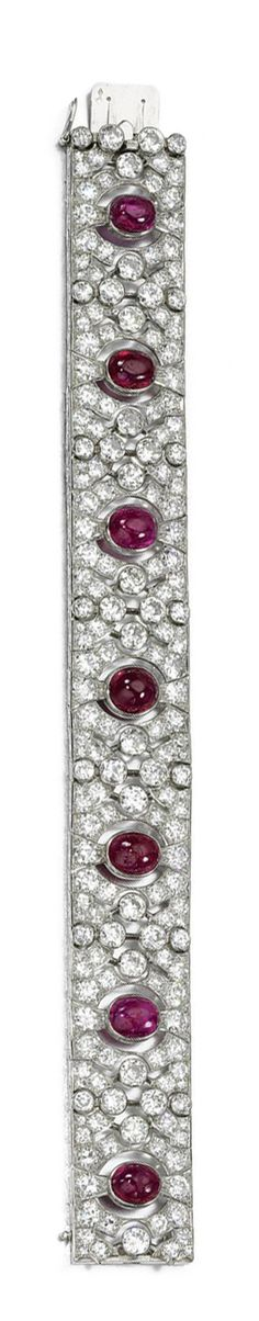 RUBY AND DIAMOND BRACELET, VAN CLEEF & ARPELS, CIRCA 1920.  The articulated open work band centrally set with seven cabochon rubies, highlighted with circular- and single-cut diamonds, length approximately 180mm, signed Van Cleef & Arpels and numbered, French assay and maker's marks.