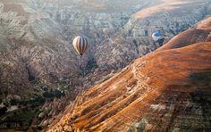Hot air balloons explore a valley nearby Goreme in Cappadocia, Turkey.