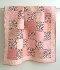 This adorable baby girl quilt is made of soft cotton solid and floral fabrics. The backing and binding are made with coordinating prints. This quilt measures 42 x 47, the perfect size for a crib quilt and snuggling with your little one. It would make a lovely accent piece for a little girls room.  This beautiful quilt was pieced and longarm quilted in my studio. The extensive quilting fills the lovely peachy-pink prints with flower blossoms. The binding is double folded with mitered corners…