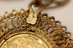 After conservation treatment.   Woman's necklace or head ornament in gilded metal; a double chain formed of pairs of filigree rosettes with an applied lozenge at the join, ending in triangular filigree clasps with hook and eye fittings, each set with a red glass stone and a further applied lozenge. From the lower row of rosettes are suspended five coins of Peter II of Yugoslavia (1934-45) all dated 1938: two 50 para, two 1 dinar and one 2 dinar piece, each with Kraljevina Jugoslavija…