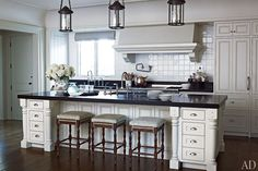 The kitchen of a Marin County, California, home was given a dose of traditional elegance by designer Suzanne Rheinstein and architect Ken Linsteadt. The custom-made Paul Ferrante lantern-style lights, granite countertops, and walnut floors contrast with the cream-color backsplash tile, cabinetry, and walls. (December 2011)