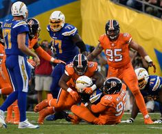 Broncos vs. Chargers:   October 13, 2016  -  21-13, Chargers   -       Denver Broncos inside linebacker Todd Davis (51) and Denver Broncos nose tackle Sylvester Williams (92) wrap up San Diego Chargers running back Melvin Gordon (28) during the second quarter October 13, 2016 at Qualcomm Stadium in San Diego, Calif.