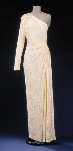 Designed by Hachi for the Princess of Wales, she wore this one-shoulder white columnar dress embroidered all over with translucent glass beads and crystals to the film premiere of Octopussy in 1983. Diana also wore it in Washington D.C. in 1984, and also on a state visit to Japan. Lot #20 was purchased by 'You' magazine and it raised $ 75,100 for Diana's charities. It was available on a Franklin Mint limited edition doll in Diana's likeness, although with far less beading than the original.