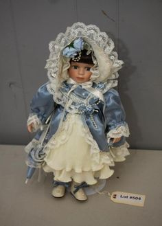 """Angelina Collection porcelain doll by Treasure doll having brown hair wearing blue dress with lace, with COA """"Angelina Collection by Treasure this fine porcelain doll is an original artistic collection designed especially for the most serious collector"""" on back, 9"""" x 19""""T."""