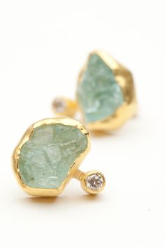This organic earring features an 8mm rough cut aquamarine bezel set in 18kt yellow gold.  A small rose-cut what diamond is attached to the side for a bit of asymmetrical intrigue.