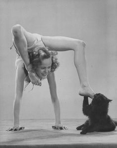 Gjon Mili's cat Blackie nibbling young acrobat's foot as she does a  handstand.