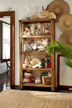 I love how this entire bookshelf pays tribute to the Coastal Look.  The straw hats are a great contrast, that way it doesn't seem overdone, it is allot of shells after all, so you really need something in the background to offset all the shells.