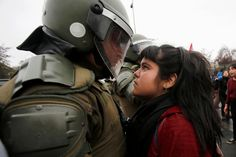 Little Mama stands up to riot police in Chile. GREAT photo!