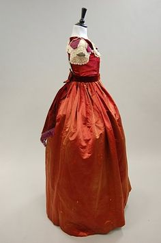 A copper-red satin gown with day and evening bodice. 1860s.