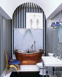 BATHROOM GALLERY    The master bath's nickel-and-brass tub is 19th century, and the chair is by Honoré Paris from Galerie Yves Gastou; the wall stripes are painted.    Featured in: Paris Match