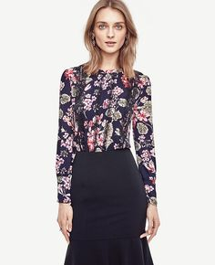 """Intricate lace pretties up this pintucked blouse, popped with winter florals. Jewel neck with ruffle collar. Long sleeves with shirred sleeve caps, shirred cuffs and button closure. Front pintucks. Front top applied lace. Back slit with button closure. Shirttail hem. 26"""" long."""