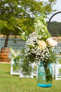 Our ceremony decor - flowers hanging in blue mason jars and a whiskey barrel. :) #ChristaMitchellPhotography #wedding #lake