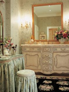 Elegant and ornate furniture create a luxurious feel in this spacious bathroom. A gold framed mirror and layers of floral patterns are rich accents that are hallmark of traditional design.