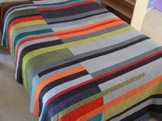 "The design is modern and minimal, the colors are reminiscent of the 50's and 60's, the end result is this quilt. It is, as you can see, constructed of bands of colors - graduations of greys and greens, highlighted with bright warm red and oranges with just a touch of teal. It is machine pieced and the top is free-motion quilted.  This quilt pictured measures 94"" x 84""* (approx) and it 100% cotton - top, back and batting. It fits perfectly on a queen or full size bed (It lays on a full sized…"