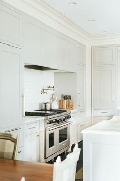 White and gray kitchen features a light gray paneled vent hood placed over a swing-arm pot filler and a stainless steel stove flanked by light gray stacked cabinets.