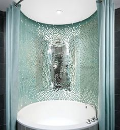 Designed by the legendary Philippe Starck, the bathtubs at the Royalton Hotel in New York are surrounded by shimmering glass tiles that reflect the aqua and slate color schemes of the room. So refreshing.