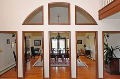 Architectural doorways and windows into dining room from foyer.