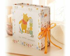 A timeless keepsake box for those precious baby mementos. Decorated with the classic Winnie The Pooh design and finished with a satin ribbon. Open the box & inside are little labelled drawers, each to place a different memento: - my precious things - my dummy - my first mittens - my hospital bracelet - my bits & bobs - my treasures - my first shoes - my first scan Overall size - H22.5 x W22.5 x D9cm.