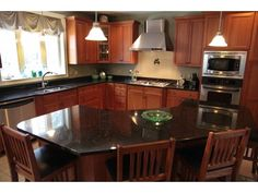 Tiled, spacious kitchen with granite and SS appliances including a wall oven and large stove hood.- Esther, Bedford, NH real estate as presented by Verani Realty.