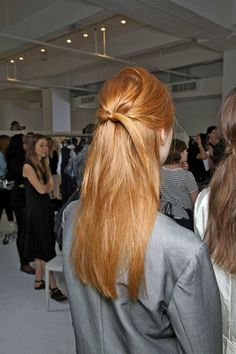Pull hair into a half-up ponytail and secure with a small rubber elastic. Loop ponytail through the base (under the elastic) to create the illusion of a knot.
