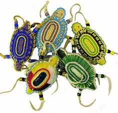 Artist, Kevin D. Fast Horse, honors American Indian tradition with these colorful beaded turtle amulets.  Description  According to Native American tradition, the turtle was honored by the Lakota people because it represented good health and a long life; its shell symbolized protection. The turtle's special power and stature were conferred to the owner of objects displaying the turtle emblem. The amulets are made from leather and is done with hand-cut Italian glass beads. Oglala-Lakota