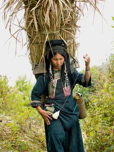 """An Akha Nuquie woman spinning cotton as she returns to her village from the forest, Phongsaly province."""