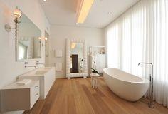 Badezimmer mit Hartholz-Boden und freistehender Badewanne