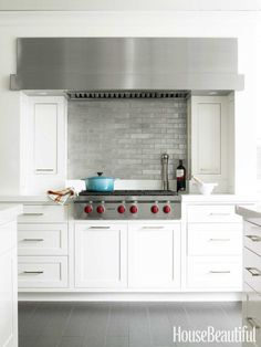 The custom hood extends beyond the span of the 36-inch Wolf cooktop for a more contemporary look. Inca tiles in Brushed Aluminum from Ann Sacks.   - Veranda.com